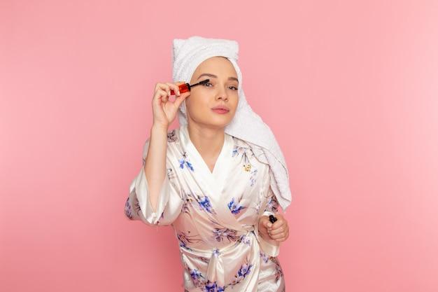 Вид спереди молодая красивая дама в халате делает макияж