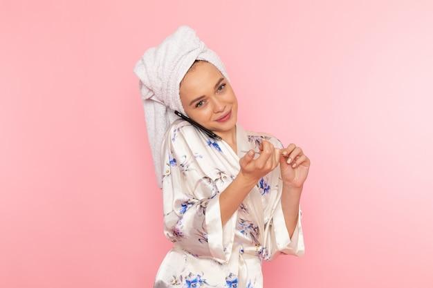 Вид спереди молодая красивая дама в халате поправляет ногти и разговаривает по телефону