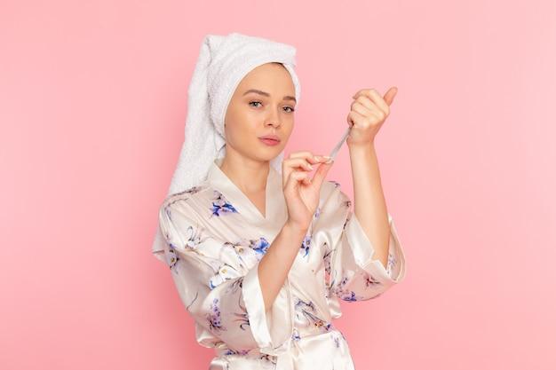 彼女の爪を修正するバスローブの正面の若い美しい女性