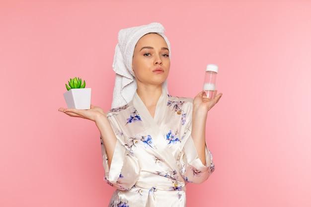 植物とフラスコを保持しているバスローブで正面の若い美しい女性