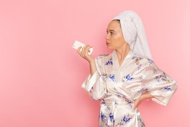 Вид спереди молодая красивая дама в халате держит пульт дистанционного управления
