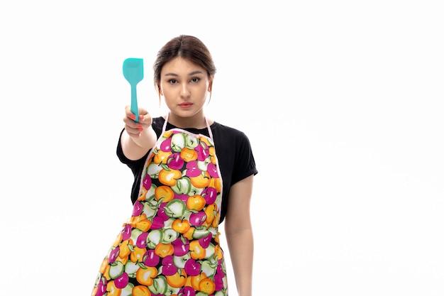 Вид спереди молодая красивая дама в черной рубашке и красочной накидке держит синий кухонный прибор мышления