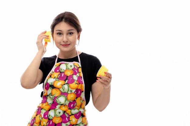 Вид спереди молодая красивая дама в черной рубашке и разноцветной накидке держит улыбающиеся желтые маленькие кастрюли
