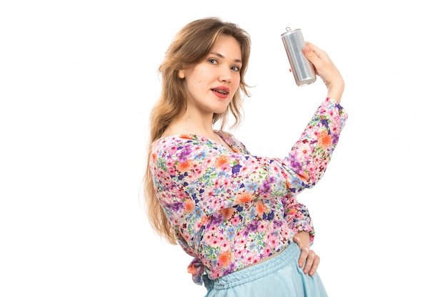 Вид спереди молодая красивая дама в разноцветной рубашке с цветочным рисунком и синей юбке с серебряной банкой на белом