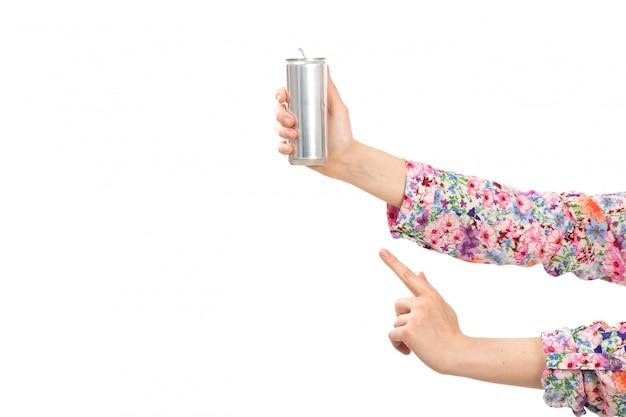 Вид спереди молодая красивая дама в красочном цветочном дизайне рубашки с серебряной банкой показывает пальцем на белом