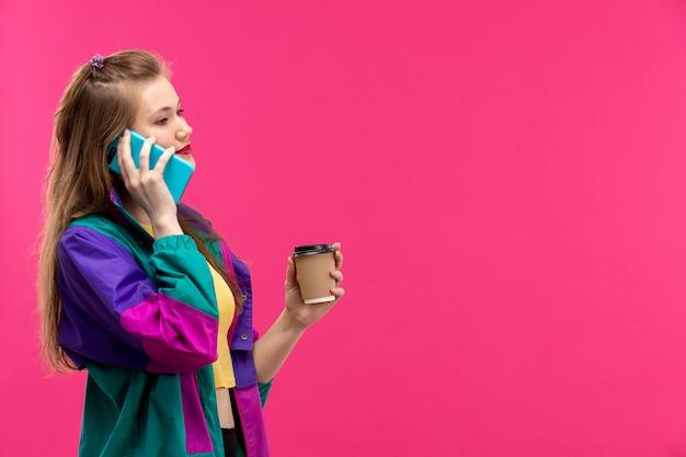 Вид спереди молодая красивая дама в красочной куртке оранжевого цвета рубашки черные брюки, улыбаясь, разговаривает по телефону, держа кофе