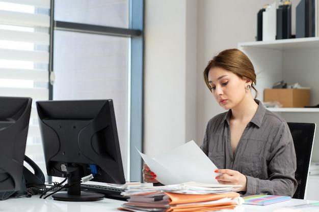 Вид спереди молодая красивая дама в серой рубашке работает с документами, сидя в ее офисе во время дневного строительства
