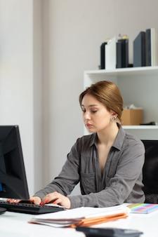 Вид спереди молодая красивая дама в серой рубашке работает с документами, используя ее компьютер, сидящий внутри ее офиса в дневное время, строя работу