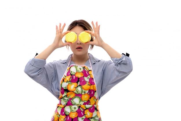 Вид спереди молодая красивая дама в светло-голубой рубашке и разноцветной накидке, закрывающая глаза желтыми сковородками