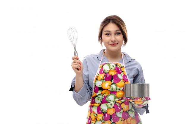 水色のシャツとシルバーケーキパン幸せな笑顔式を保持しているカラフルなケープの正面の若い美しい女性
