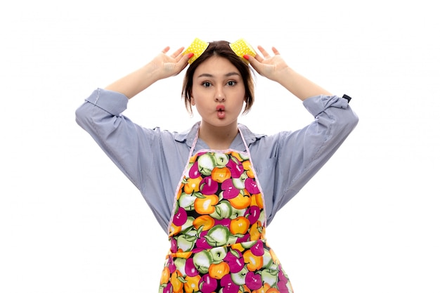 Вид спереди молодая красивая дама в светло-голубой рубашке и разноцветном плаще, держащем желтые сковородки с забавным выражением лица