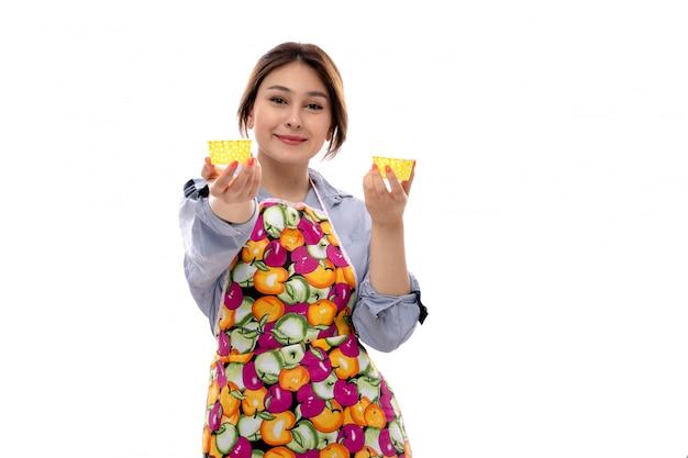 Вид спереди молодая красивая дама в светло-голубой рубашке и красочной накидке держит желтые сковородки, улыбаясь