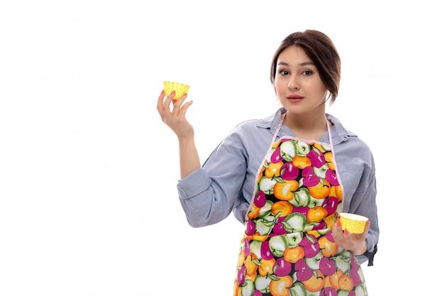 Вид спереди молодая красивая дама в светло-голубой рубашке и красочной накидке с желтыми сковородками