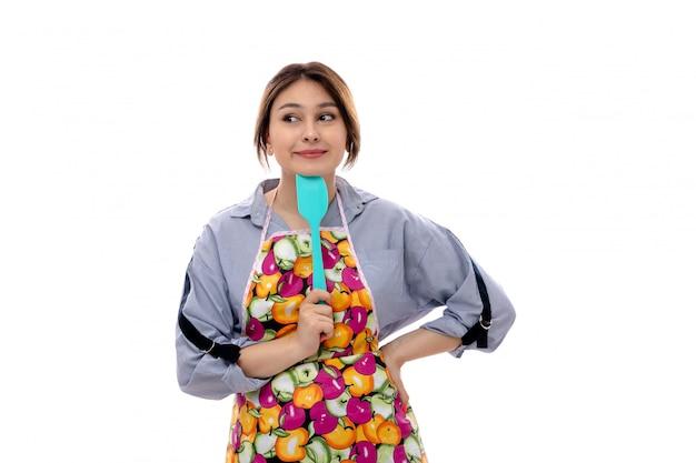 水色のシャツと笑みを浮かべて青いキッチンアプライアンスを保持しているカラフルなケープ思考で正面の若い美しい女性