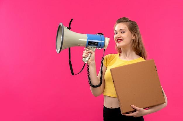 Вид спереди молодая красивая дама в оранжевой рубашке черные брюки, улыбаясь, держа мегафон и пакет