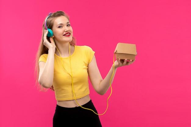 Вид спереди молодая красивая дама в оранжевой рубашке черные брюки, улыбаясь, слушая музыку