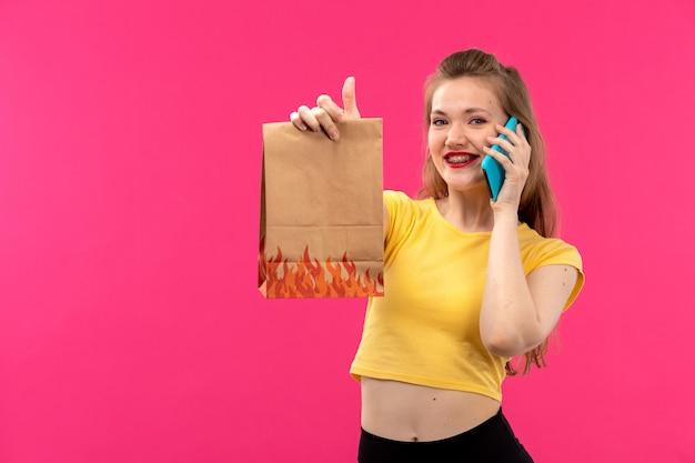 パッケージを保持している電話で話している笑顔オレンジ色のシャツ黒ズボンの正面の若い美しい女性