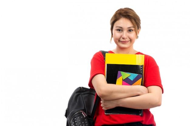 別のコピーブックと白のバッグを浮かべてファイルを保持している赤いtシャツブラックジーンズの正面の若い美しい女性