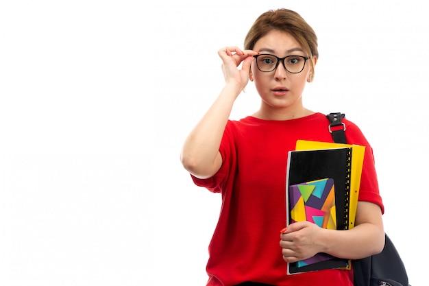 白のバッグと異なるコピーブックとファイルの眼鏡を保持している赤いtシャツブラックジーンズの正面の若い美しい女性