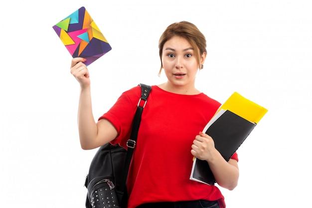 別のコピーブックと白のバッグを持つファイルを保持している赤いtシャツブラックジーンズの正面の若い美しい女性
