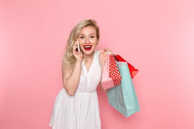 Вид спереди молодая красивая дама в белом платье держит пакеты покупок, разговаривает по телефону с улыбкой на лице