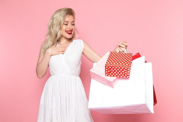 彼女の顔に笑顔でショッピングパッケージを保持している白いドレスの正面の若い美しい女性