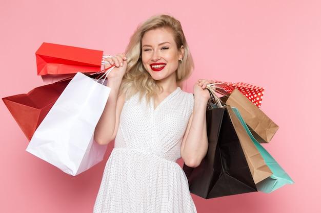 Вид спереди молодая красивая дама в белом платье держит пакеты с улыбкой на лице