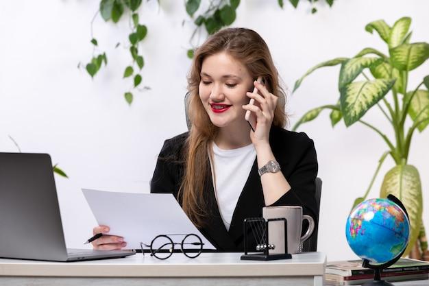 Вид спереди молодая красивая дама в белой рубашке и черной куртке, используя свой ноутбук перед столом, улыбаясь, разговаривает по телефону, работая с документами