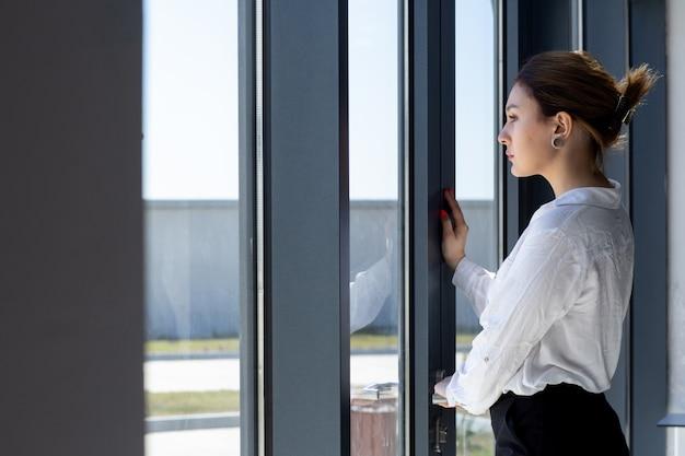 Вид спереди молодая красивая дама в белой рубашке черные брюки, глядя на расстояние через окно в холле, ожидая в дневное время, строя работу