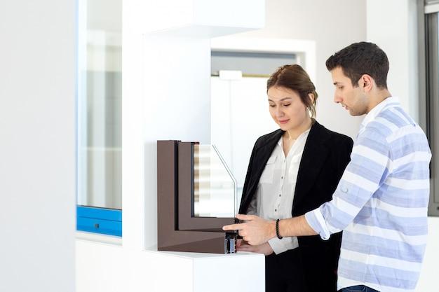 昼間の建物の仕事の活動中に何かを議論する若い男と一緒に白いシャツダークジャケット黒ズボンで正面の若い美しい女性