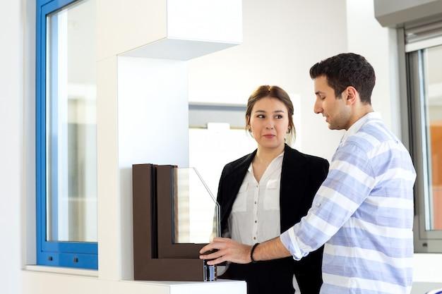 昼間の建物の仕事の活動中に仕事を議論する若い男と一緒に白いシャツダークジャケット黒ズボンの正面の若い美しい女性