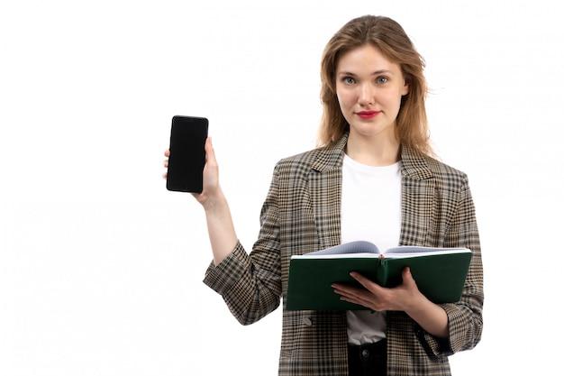 白いtシャツの黒のジーンズと白の黒のスマートフォンと緑の本を保持しているコートの正面の若い美しい女性