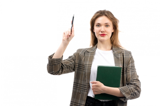 白いtシャツの黒のジーンズと白で笑顔の緑の本を保持しているコートの正面の若い美しい女性