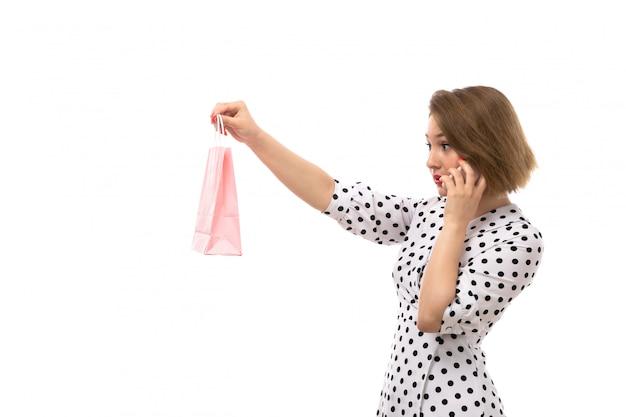電話で話しているポーズのショッピングパッケージを保持している黒と白の水玉ドレスの正面の若い美しい女性