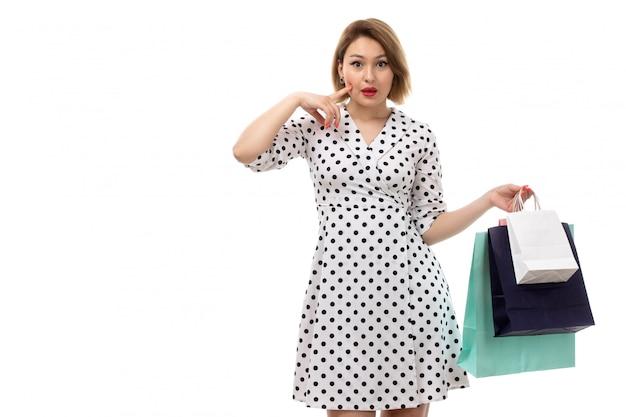 ショッピングパッケージのポーズを保持している黒と白の水玉ドレスの正面の若い美しい女性