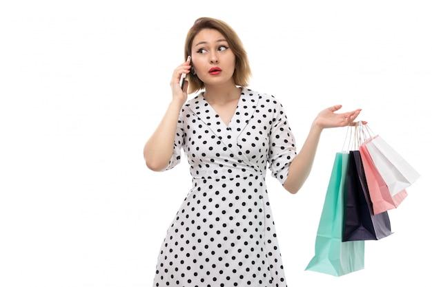 電話で話しているショッピングパッケージを保持している黒と白の水玉ドレスの正面の若い美しい女性