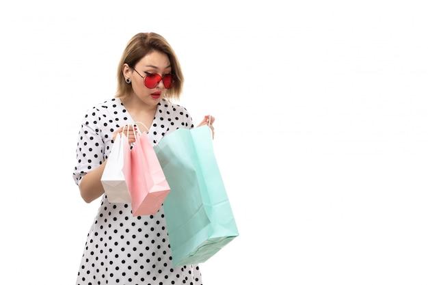 驚いた表情をポーズショッピングパッケージを保持している赤いサングラスの黒と白の水玉ドレスの正面の若い美しい女性