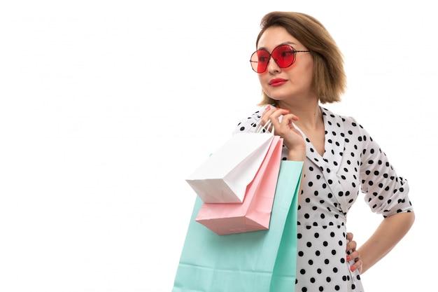 ショッピングパッケージのポーズを保持している赤いサングラスの黒と白の水玉ドレスの正面の若い美しい女性