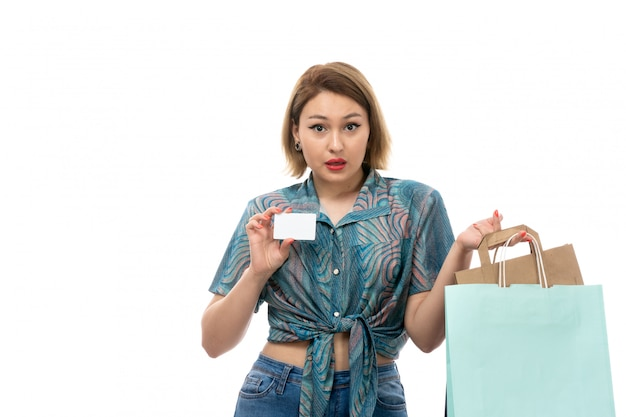 흰색 카드를 보여주는 쇼핑 패키지를 들고 컬러 블라우스 청바지에 전면보기 젊은 아름다운 여자