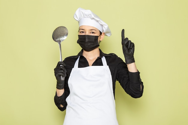 Вид спереди молодая женщина-повар в черной рубашке белая поварская накидка белая шапка в черных перчатках черная маска с большой серебряной ложкой
