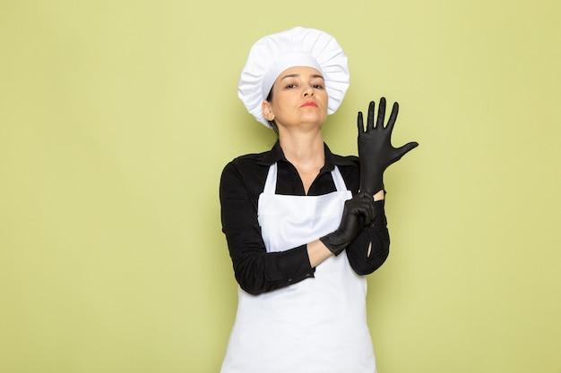 Вид спереди молодая женщина повар в черной рубашке белый повар плащ белая шапка позирует черные перчатки позирует