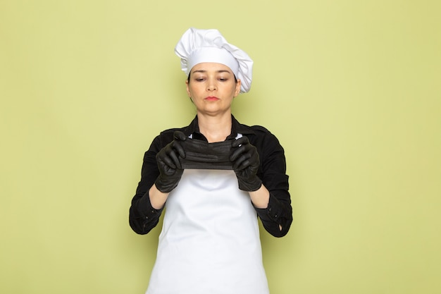 正面を向いた若い女性クックブラックシャツホワイトクックケープホワイトキャップポーズを黒い手袋weanig黒マスクポーズ