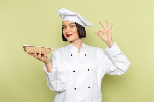 Молодая женщина-повар, вид спереди, в белом костюме повара и кепке держит миску с улыбкой на зеленой стене