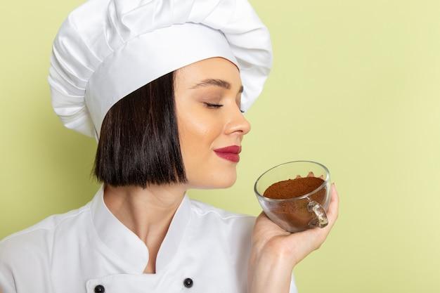 緑の壁に白いクックスーツと粉末コーヒーのカップを保持しているキャップで正面の若い女性クック