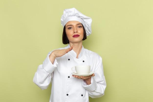 Вид спереди молодая женщина-повар в белом костюме повара и кепке держит чашку на зеленой стене