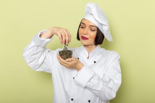 Молодая женщина-повар, вид спереди, в белом костюме повара и кепке держит чашку с сушеным чаем на зеленой стене