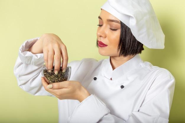 白いクックスーツと緑の壁に乾燥茶とキャップホールディングカップで正面の若い女性クック