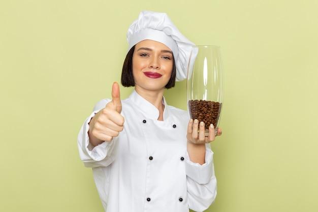 緑の壁の女性作業食品の色に白いクックスーツとコーヒーの種子が付いている瓶を保持しているキャップで正面の若い女性クック