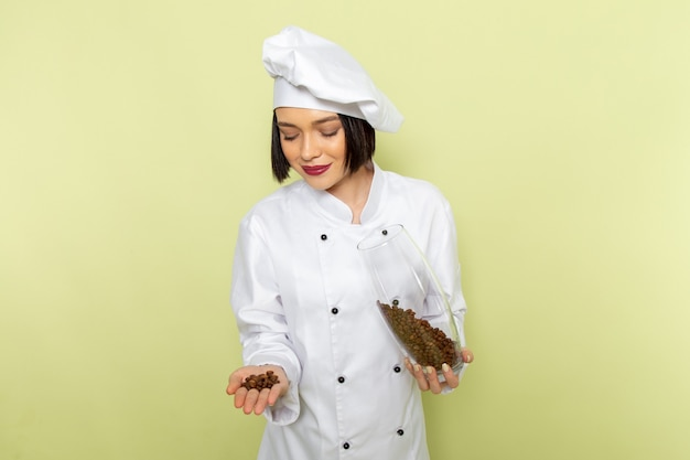 白いクックスーツと緑の壁の女性の種子にコーヒーの種子が付いている瓶を保持しているキャップで正面の若い女性クック食品料理色