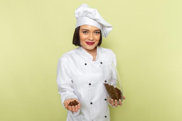 白いクックスーツと緑の壁に笑みを浮かべてコーヒーの種子が付いている瓶を保持しているキャップで若い女性クック正面女性作業食品料理色